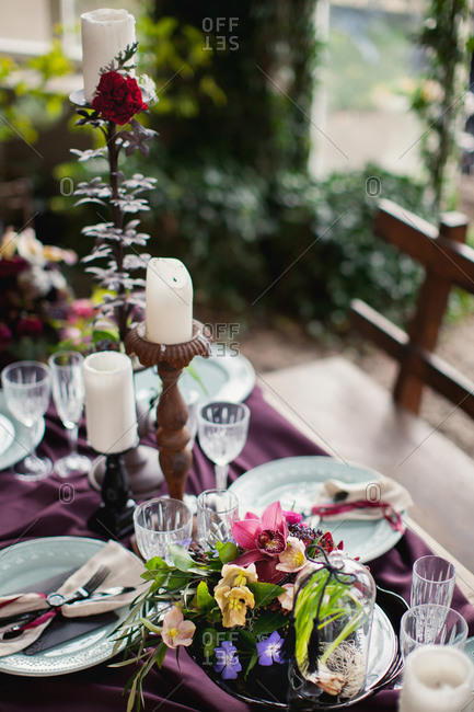 Table set with pillar candles and flower arrangements on burgundy cloth