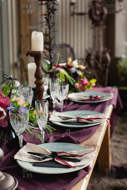 Long rustic table with burgundy cloth for set for wedding reception