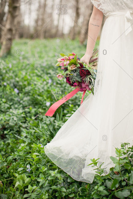 Bride with bouquet of burgundy roses standing in forest