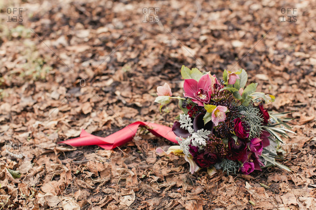 Burgundy floral bouquet resting on brown fallen leaves