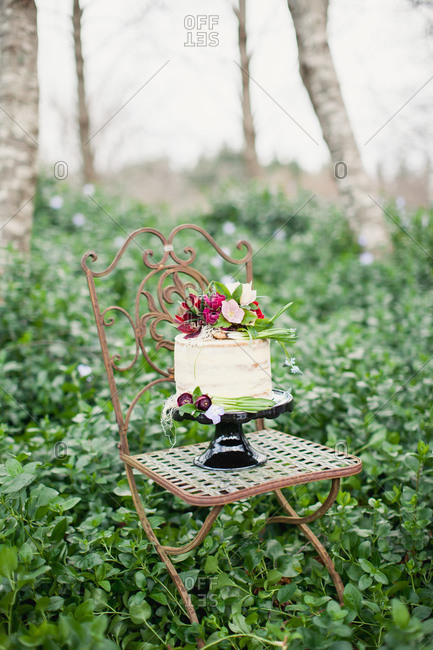 Cake decorated with burgundy flowers on chair in forest