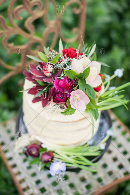 Close-up of cake topped with burgundy flowers on chair