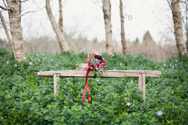 Burgundy wedding bouquet resting on rustic wooden bench in forest