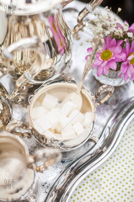 Close-up of sugar cubes in silver tea set on outdoor table