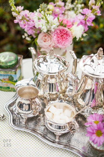 Silver tea service with pink flowers on table in garden