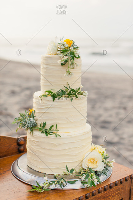 Triple tiered wedding cake decorated with yellow flowers