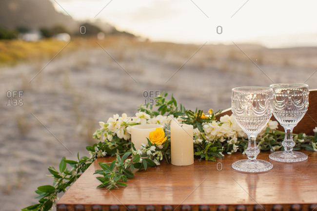 Wooden table decorated with flowers and candles with two wineglasses on beach