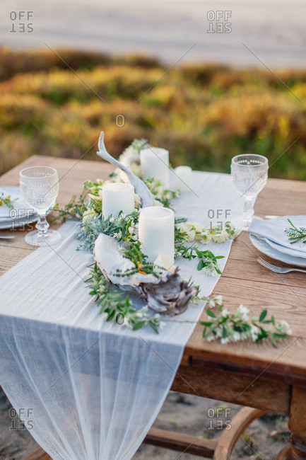Close-up of table centerpiece of candles, flowers, and driftwood on beach