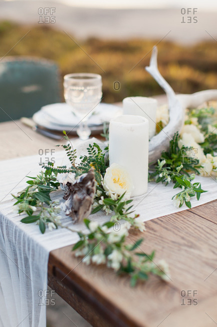 Floral centerpiece with candles on romantic table on beach