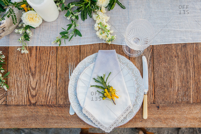 Overhead view of plate with vintage linen napkin on beachfront table