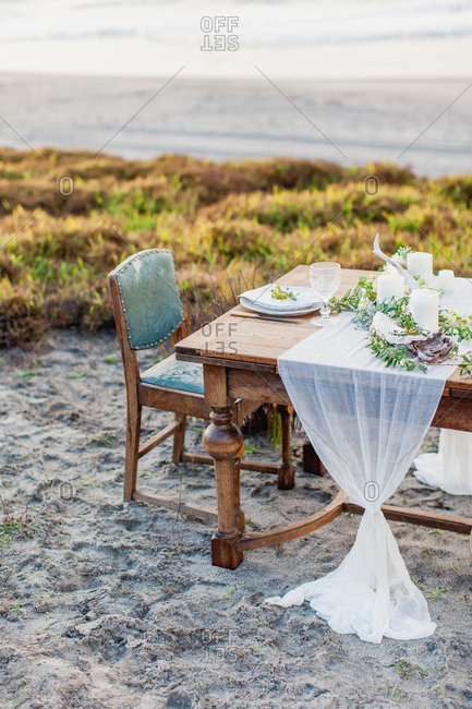 Romantic dining table set on beach at dusk