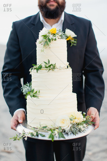 Bearded groom holding tiered wedding cake