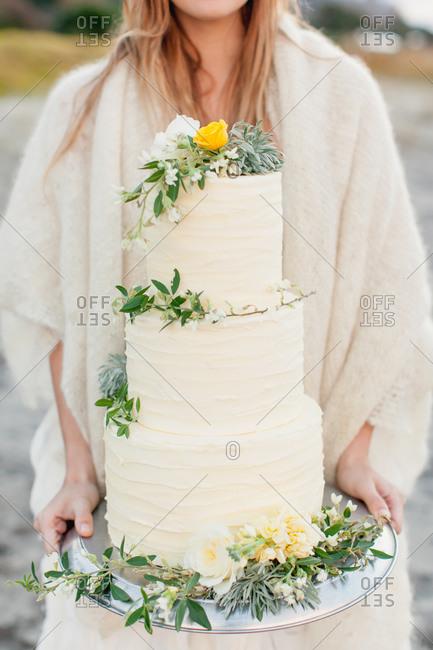 Bride holding three-tiered wedding cake