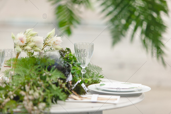 Side view of table with fern centerpiece set for wedding reception