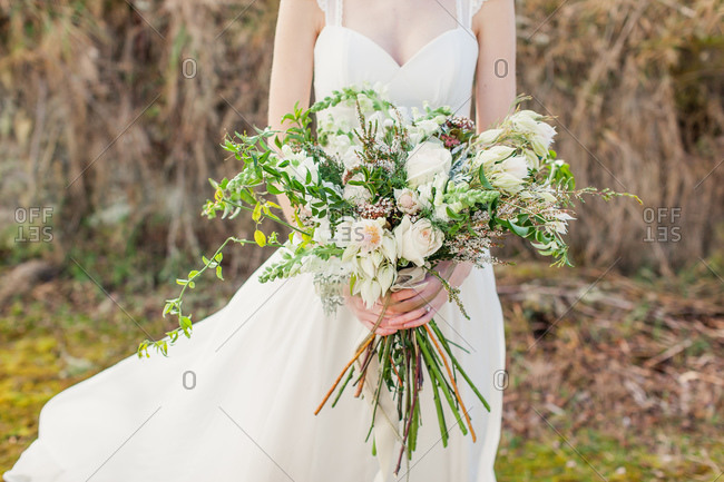 Bride holding long stemmed bouquet of roses