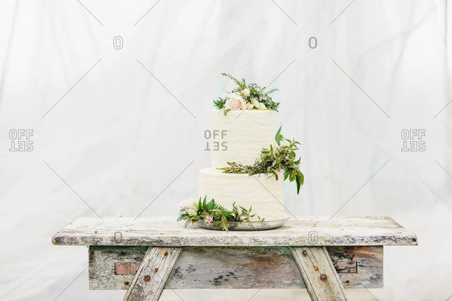 Two tiered wedding cake decorated with fresh flowers on rustic wooden table
