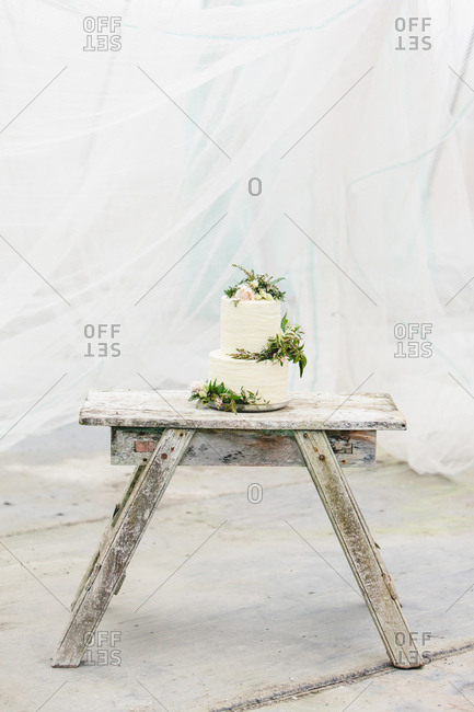 Two tiered wedding cake decorated with fresh flowers on rustic wooden bench