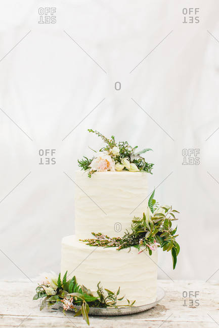 Close-up of a white frosted wedding cake decorated with fresh flowers