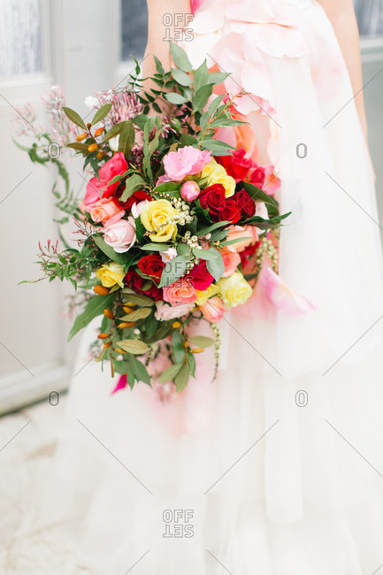 Bride in pink and white, gown holding a colorful bouquet of roses