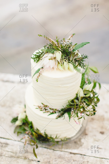 Elevated view of a white frosted wedding cake with fresh flowers