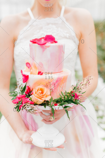 Bride in pink and white gown holding wedding cake with fresh flower decoration