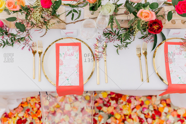 Overhead view of bride and groom place settings at table set with colorful roses