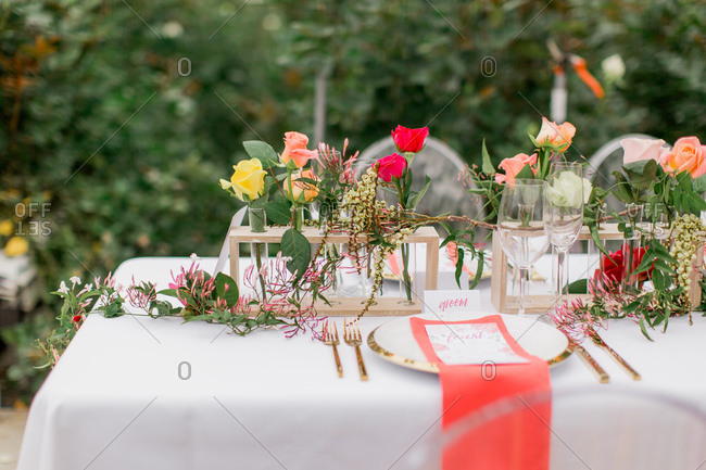Coral and pink roses in test tube vases on wedding reception table