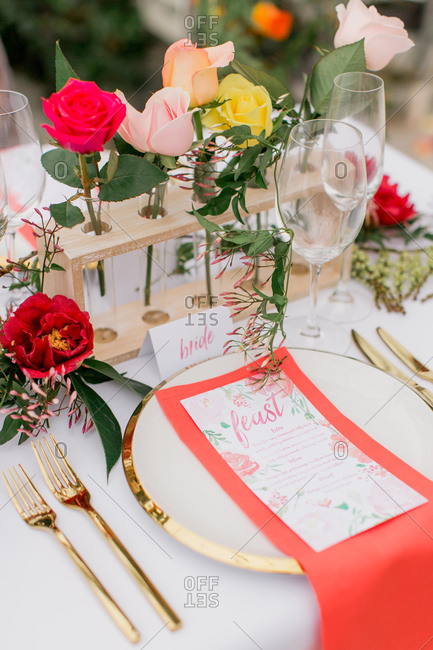 Table set with roses in test tube vases for wedding in greenhouse