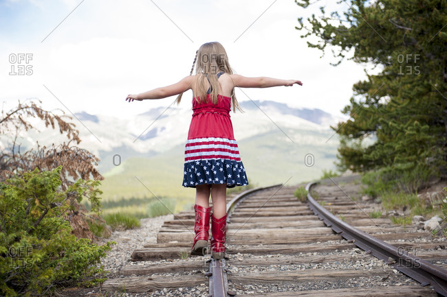 Girl wearing a stars and stripes dress and cowboy boots balances on a railroad track