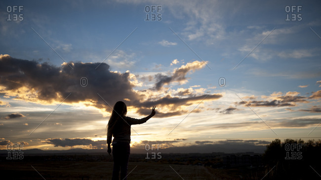 Girl standing outside making a peace sign as the sun goes down