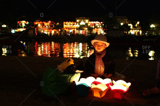 A young vietnamese boy selling floating candles to tourist by the side of the Thu Bon River, Hoi An, Vietnam