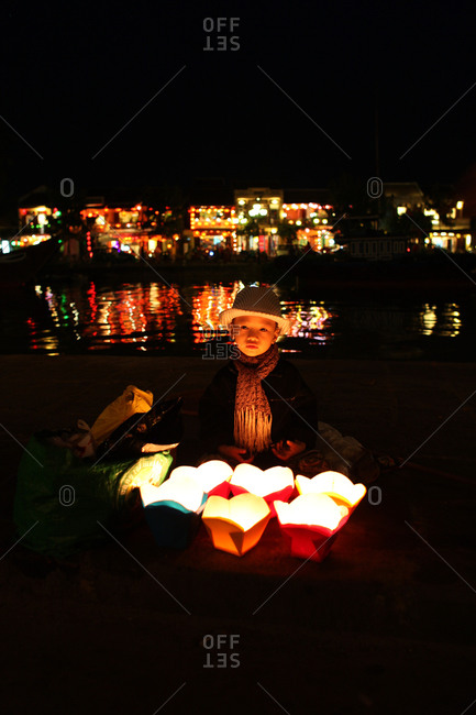A young vietnamese boy selling floating candles by the side of the Thu Bon River, Hoi An, Vietnam