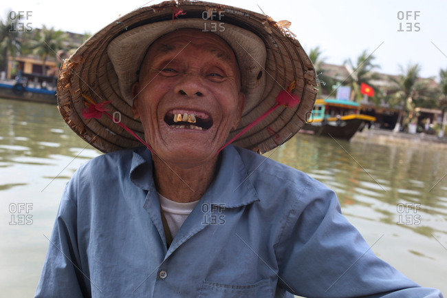 A smiling water taxi paddler at work on the Thu Bon River, Hoi An, Vietnam