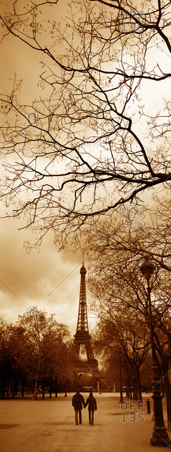 A couple walking in the  Champ de Mars park towards the Eiffel Tower in Paris, France