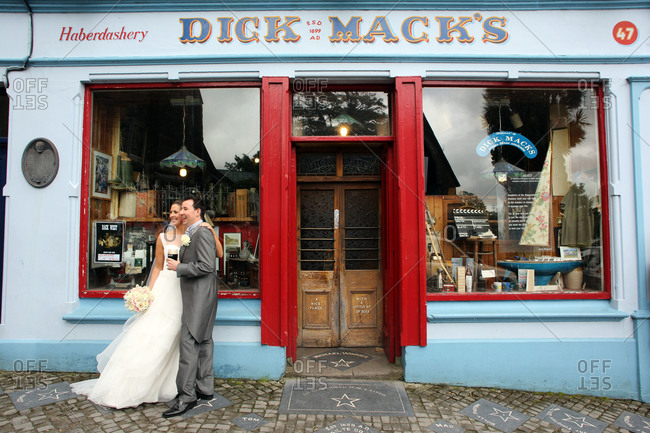 Dingle, County Kerry, Ireland - June 29, 2012: A couple celebrate their marriage with a glass of beer outside Dick Mack's pub