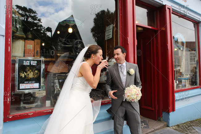Dingle, County Kerry, Ireland - June 29, 2012: A couple celebrate their marriage with a pint of beer outside Dick Mack's pub