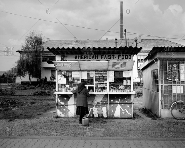 "Copsa Mica, Transylvania, Romania - November 14, 2008: A lady shops at a small ""American fast food"" kiosk in Copsa Mica, Transylvania, Romania"
