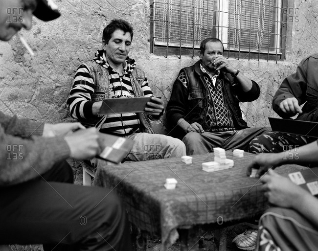 Copsa Mica, Transylvania, Romania - November 14, 2008: Men playing a game for small wagers in a housing estate in Copsa Mica, Transylvania, Romania