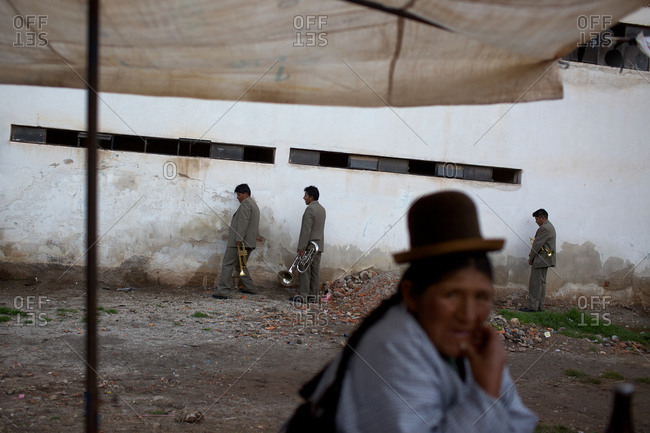 Copacabana, Bolivia - February 1, 2010: Men urinating on a wall at the festival of the Virgen de la Candelaria in Copacabana on the shores of Lake Titicaca