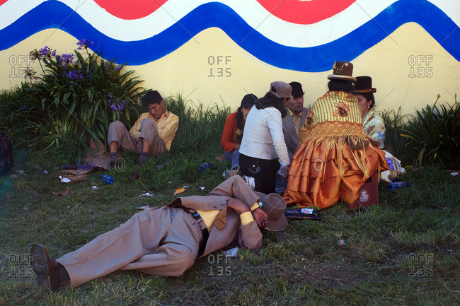 Copacabana, Bolivia - February 2, 2010: People sitting on a lawn at the festival of the Virgen de la Candelaria in Copacabana on the shores of Lake Titicaca