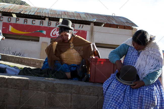 Copacabana, Bolivia - February 2, 2010: Women dressed in costumes sitting on a block wall at the festival of the Virgen de la Candelaria in Copacabana on the shores of Lake Titicaca