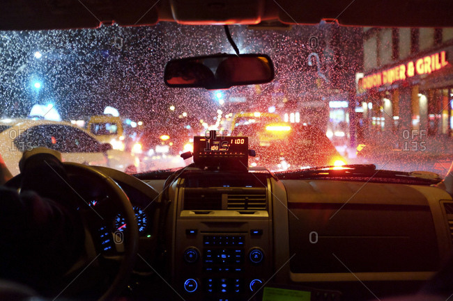 View of a city at night through the rain covered windshield of a taxi cab