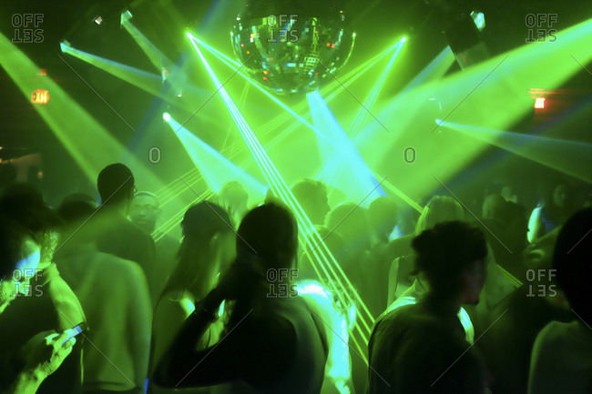 Silhouette of a crowd at a night club with mirror ball and green laser light display