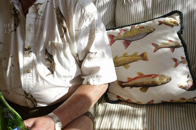 Man wearing a fish print shirt sitting on a sofa with a fish print cushion