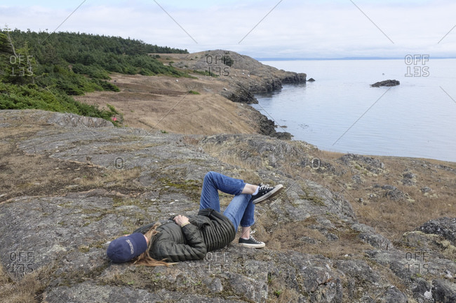 Woman wearing a jacket and baseball cap lying on a rock overlooking the ocean
