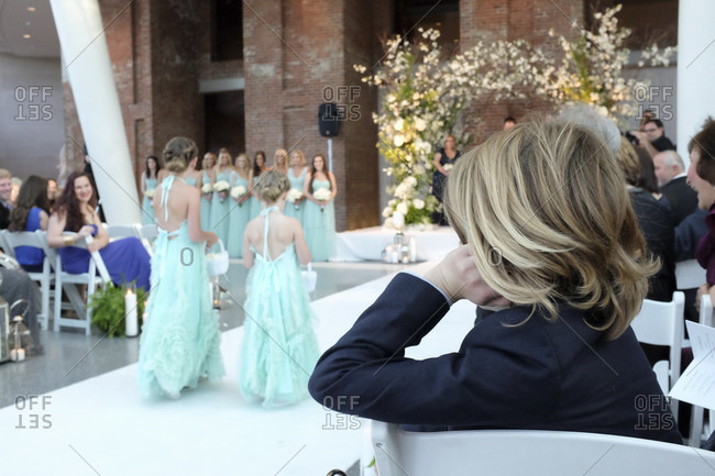 Boy watching flower girls as they walk down the aisle at a wedding