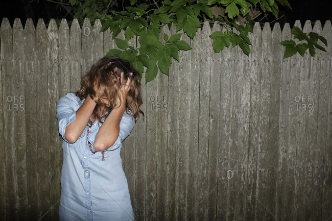 Portrait of a woman standing in front of a wood fence at night with her hands covering her face