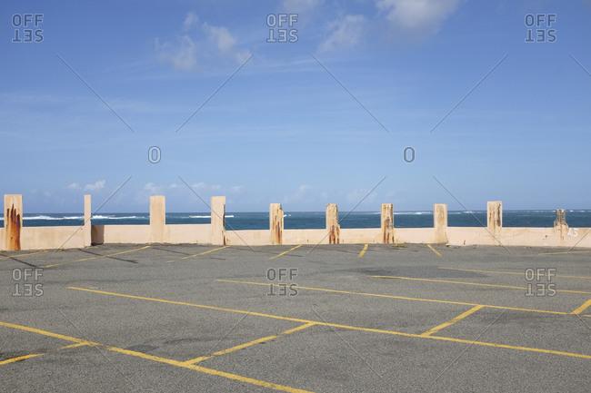 An empty parking lot alongside the ocean