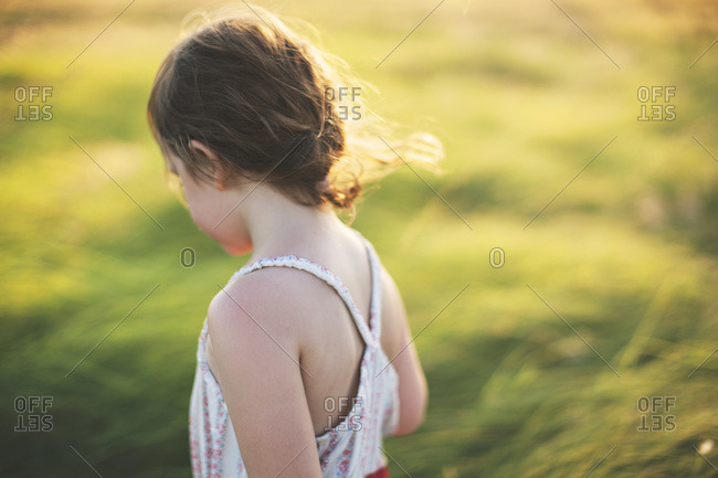 Little girl standing on a green hillside