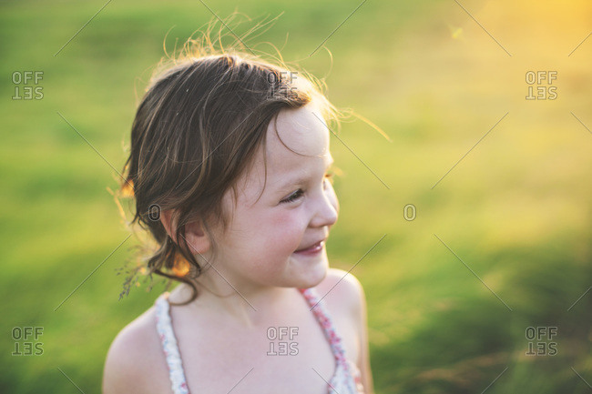 Little girl on a green hillside smiling